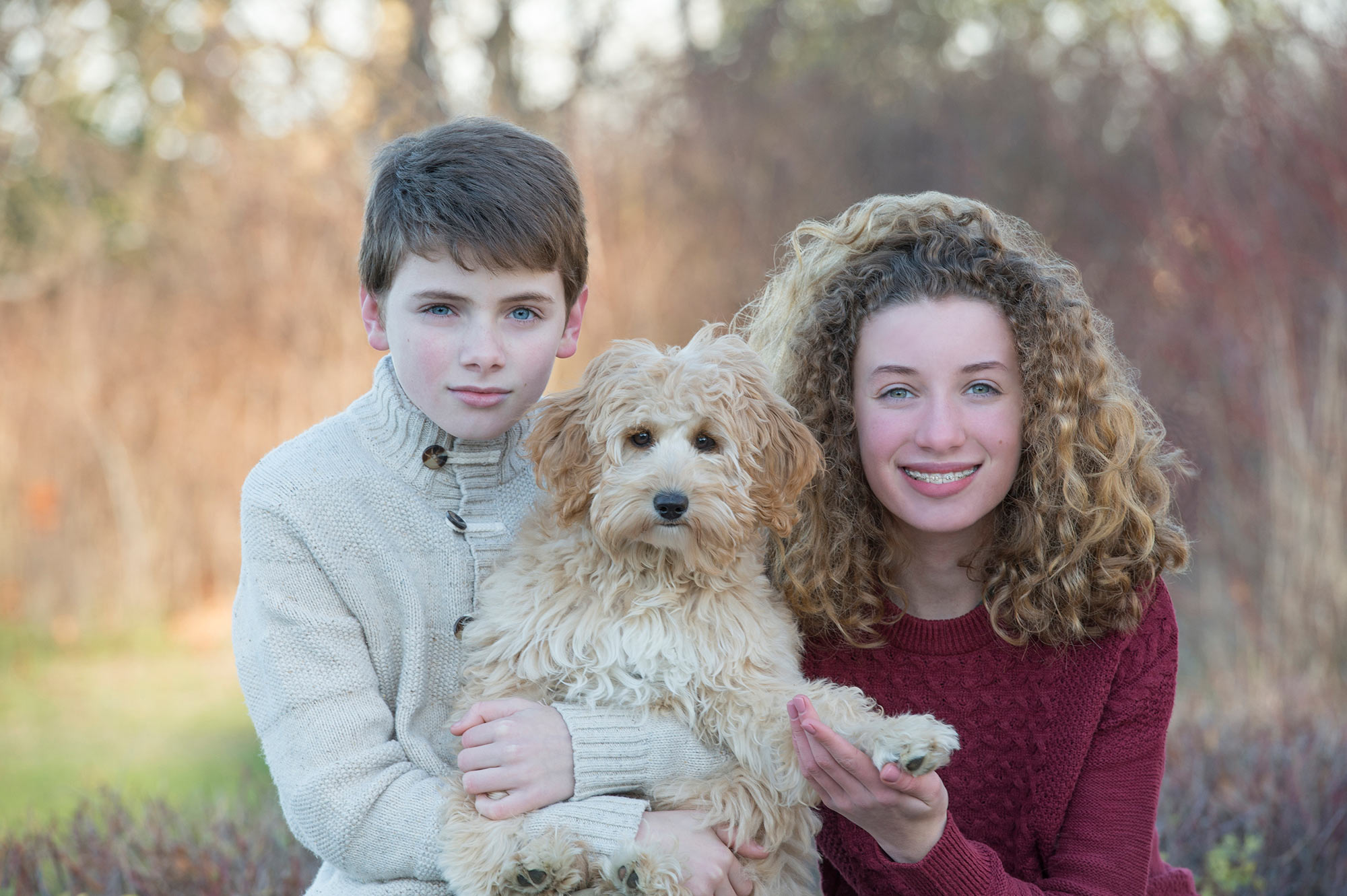 Brother and sister holding their family dog