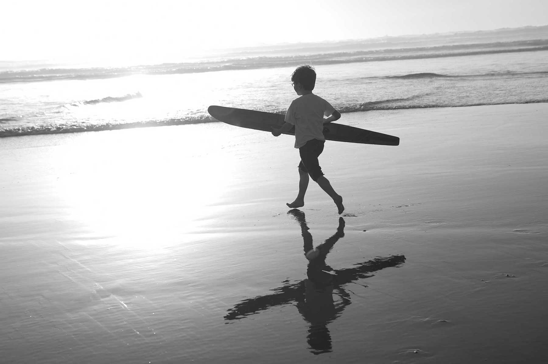 Boy running towards the Ocean with a water ski