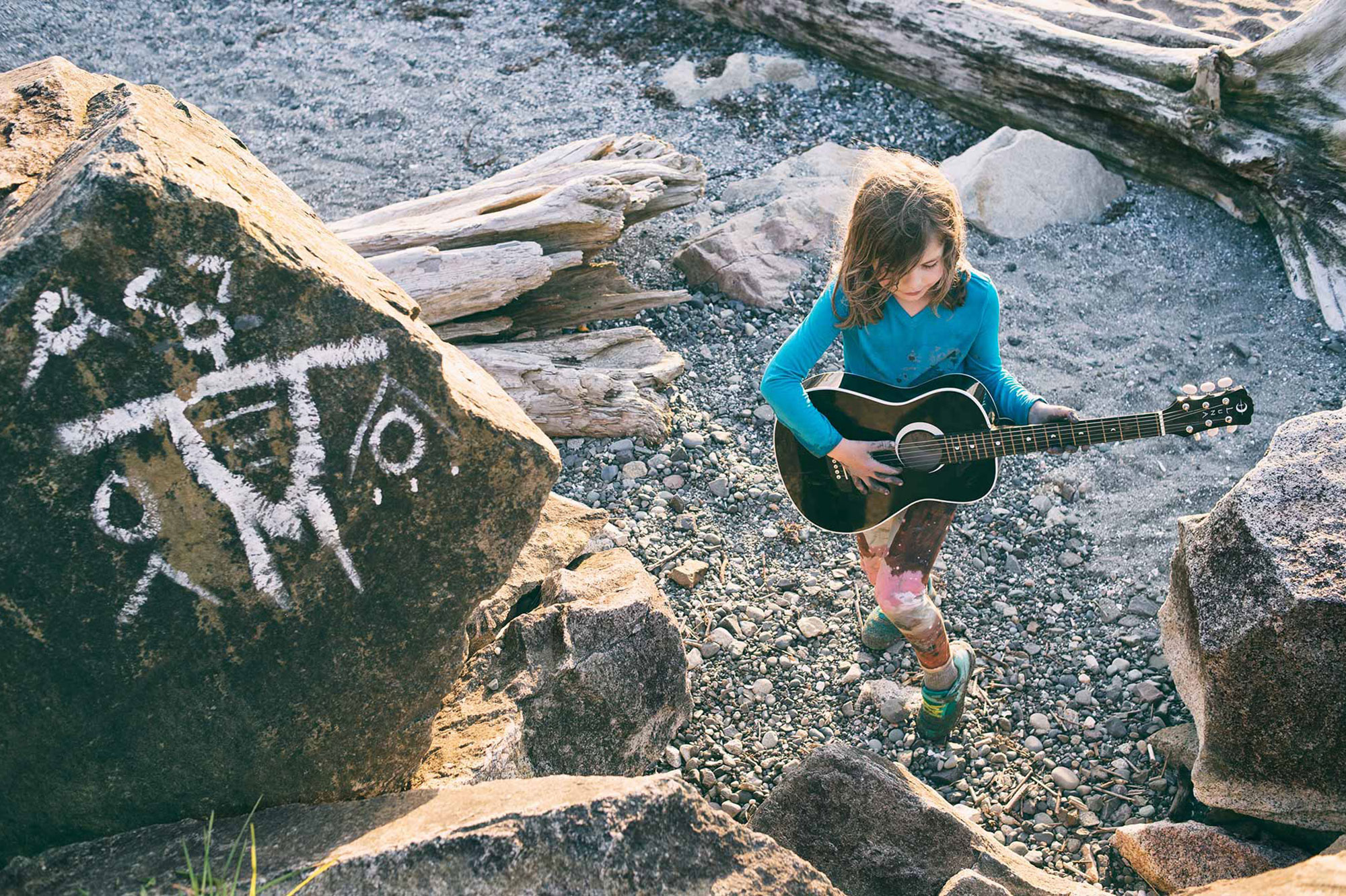 Child playing guitar at Carkeek Park in Seattle by the graffiti