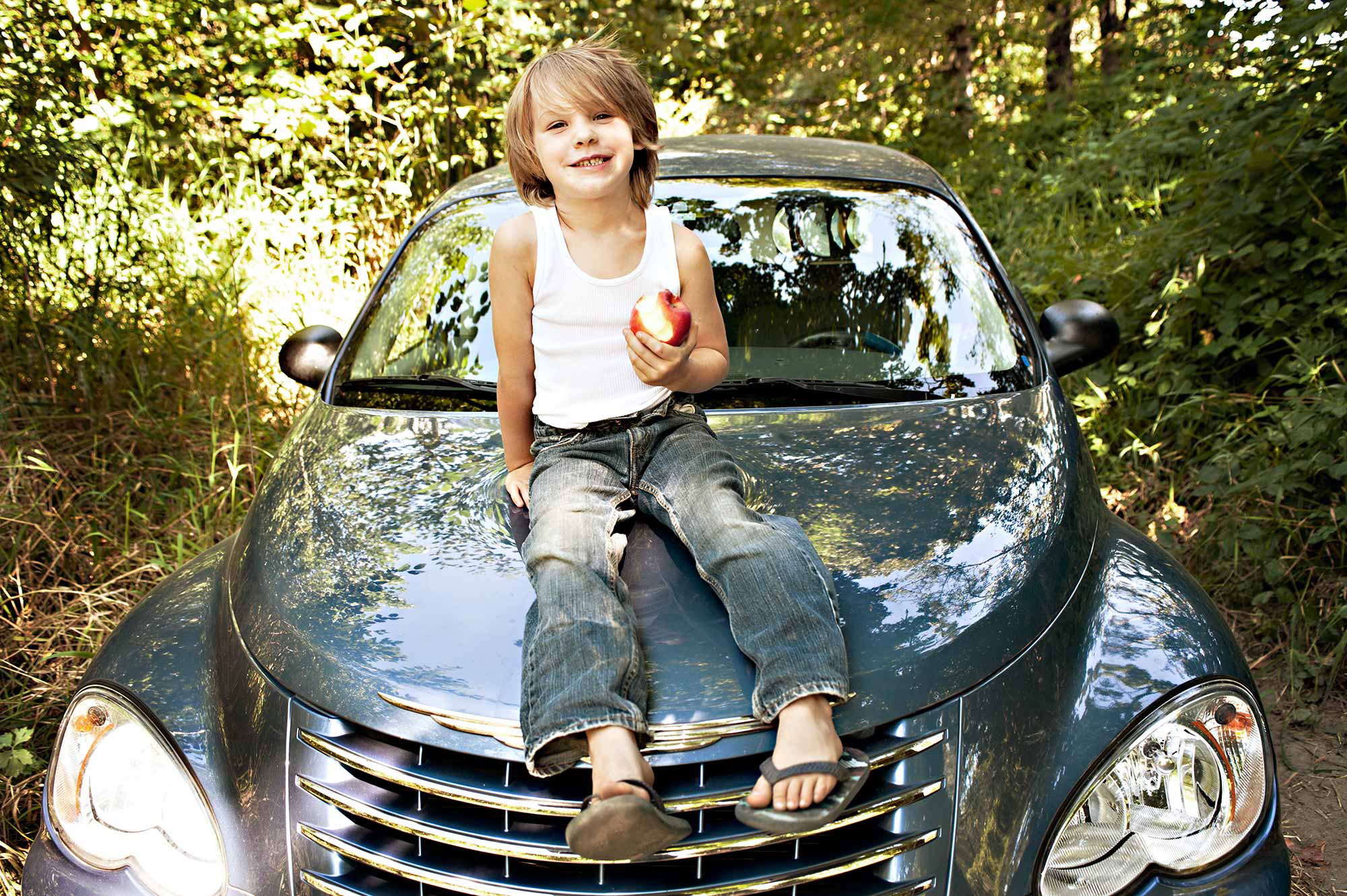 Boy eating an apple while sitting on my car. Sometimes my tolerance spreads wide.