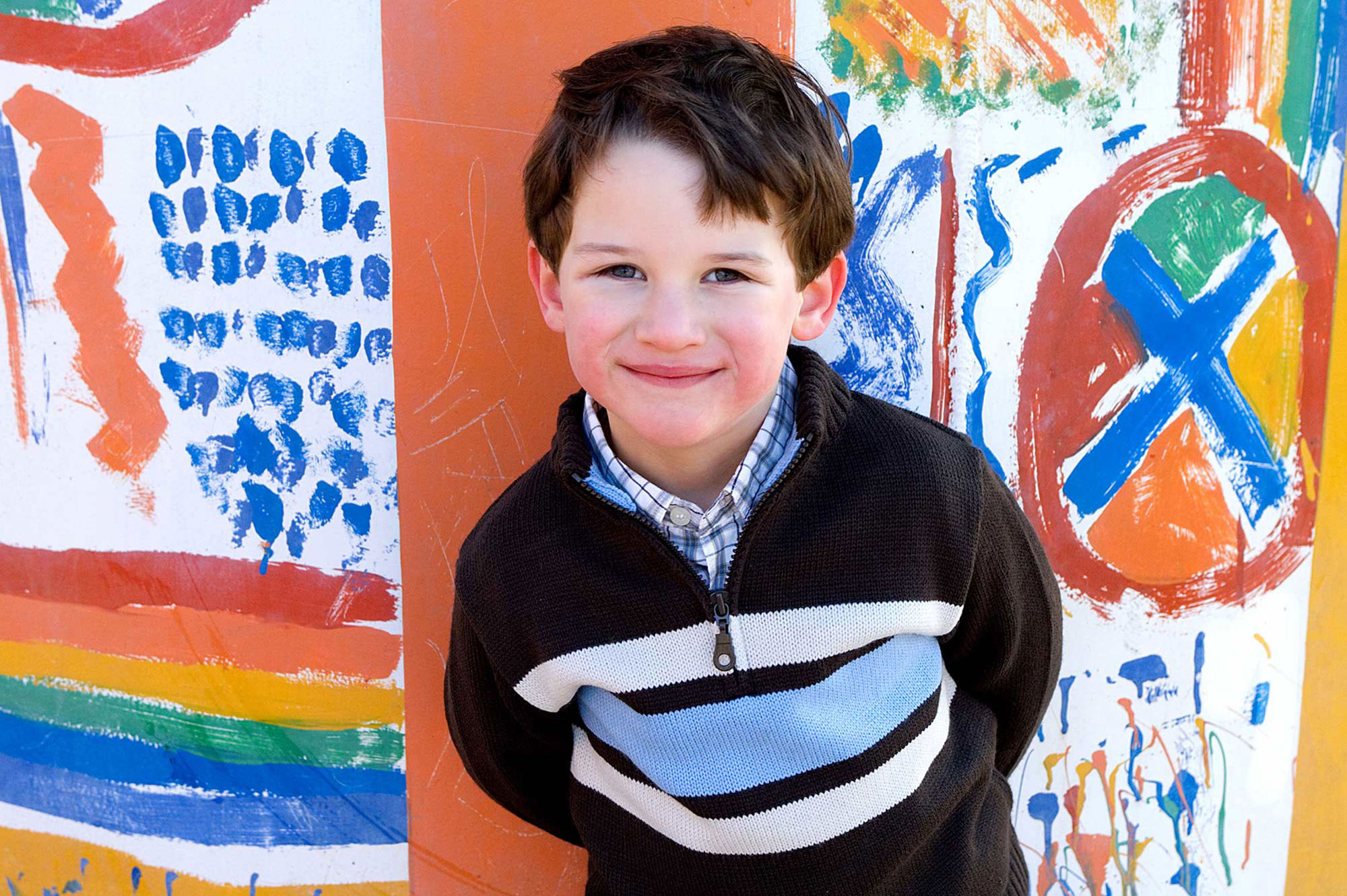 Boy standing a colorful graffiti wall and smiling gently